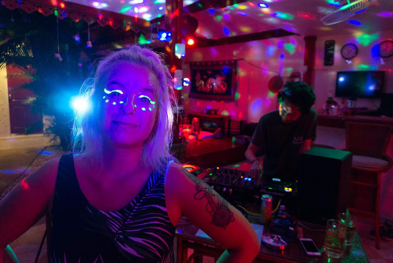 Minä kasvoillani hohtava kasvomaalaus ja taustalla DJ