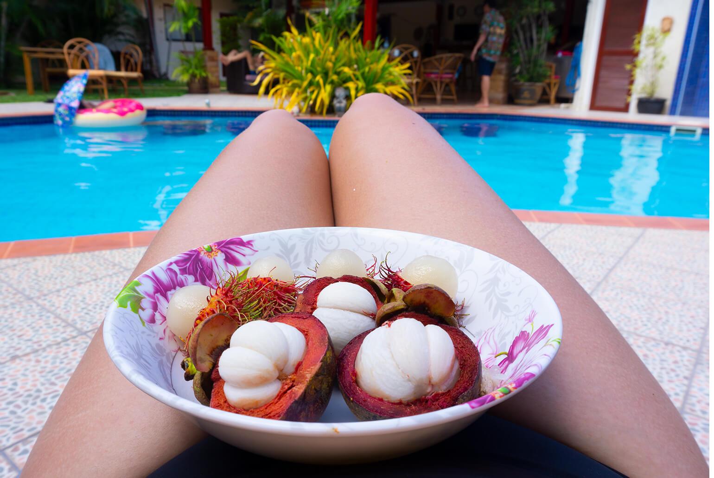 Lautanen täynnä hedelmiä ja taustalla uima-allas